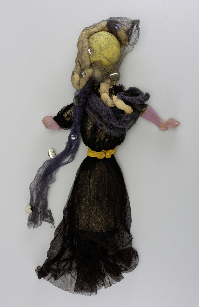 Round pink head draped in navy netting. Black gown tied at the waist with yellow.