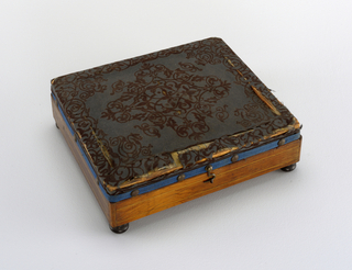 Rectangular wooden stool (a) on bun feet, with hinged lid covered in blue printed wool, mounted with upholstery nails; Rectangular tin liner (b) in stool.
