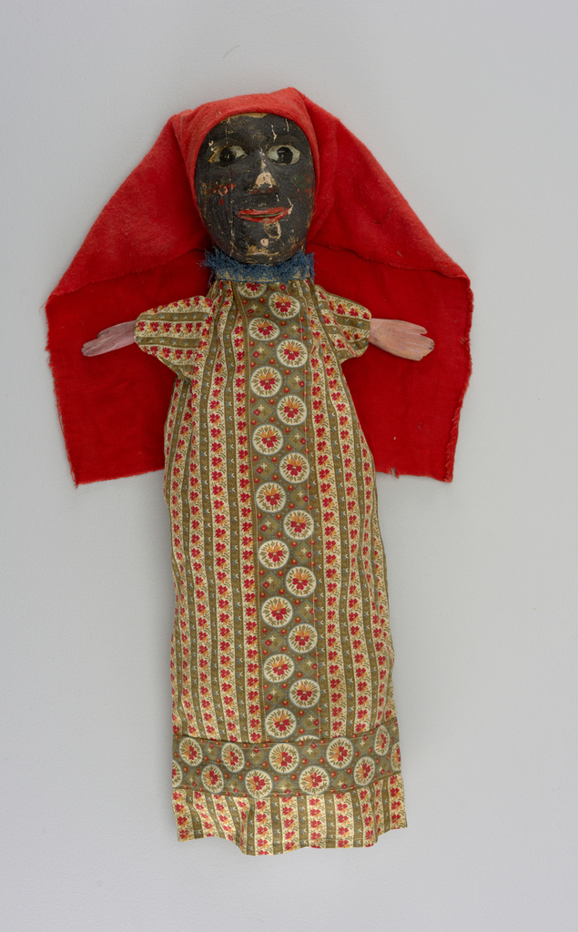 A dark skinned woman with red flannel head-cloth and printed cotton dress with blue fringe at the neck.