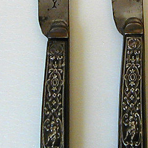Blade has straight upper edge, tapering towards the point.  Drop bolster straight handle with flaring end. Shell in center decorated on front and back with tortoise shell, inlaid with silver. Scrolls, scallops acanthus leaves, a squirrel and a man in costume on one side; a bird and a nude figure on the reverse.