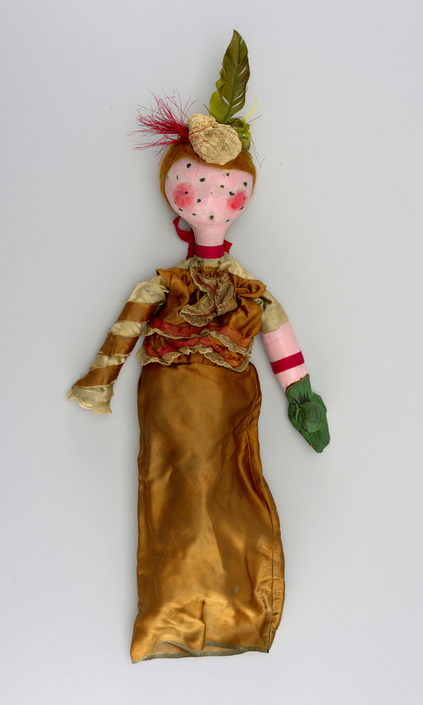 Round pink head with rosy cheeks and black spot.   Feathered headdress. Pink ribbon at neck. Ochre dress with lace. One green hand.