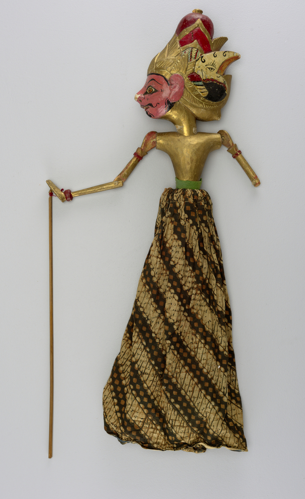 Male figure in long skirt, naked to the waist. Pink face with black moustache and beard; gold, black, red green and cream head-dress. Arms with articulated elbow. All flesh except face painted in gold. Green band at waist.