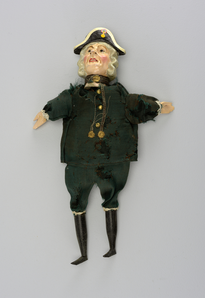 Brightly painted head with black and white bicorn with tri colored cockade. Green uniform. Black hose and shoes. Gold buttons and decorations. Lace at knees and cuffs. Possible a caricature of Admiral Nelson.