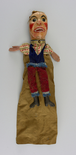 Sun-nosed head with red cheeks and open mouth. Crepe hair. Printed shirt, blue vest, red trousers, black boots. Blue fringe at ankles and waist. Blue, white and gold scrolled collar.
