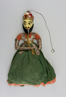 Upper torso, head and crown carved from one piece of wood and painted with red, blue, gold, and black on pale yellow. Long green skirt with red trimming over blue underskirt. Gold and silver trimming on body and arms.