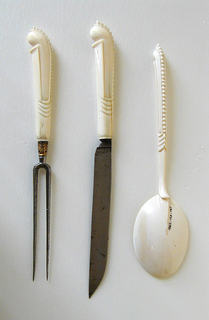 Two long straight tines, curved shoulders, neck with acanthus foliage and gilt. Pistol-shaped ivory handle carved with beaded cresting on upper side of handle. Facets and scale ornaments on the sides.