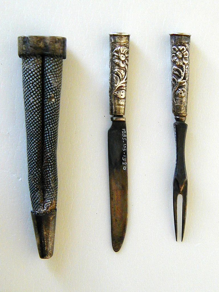 Two curved, pointed tines. Square neck, waisted in the middle. Decorated on back of join. Tapering handle, oval in section, repousse floral decoration on front and back.