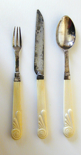 Silver fork has three curved tines, curved shoulders and flat tapering neck with diamond-shaped decoration at back of join. Plain rectangular ferrule. Pistol-shaped handle of carved ivory with beaded cresting on the top of the handle and halfway on one side. End of handle carved on the front and back with snail-shell and drop-shaped ornaments.