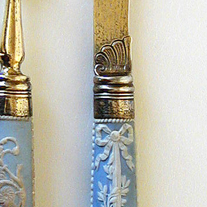 Silver-gilt sabre-shaped handle with engraved scalloped decoration on the bolster. Banded ferrule, tapering jasper handle, oval in section. Light blue ground with raised design in white, in the centre a bow and arrow, a quiver filled with arrows, a flower wreath and an incense burner surrounded with ribbons, olive twigs and a bow. Beaded cresting along the sides, floral decoration at the top of handle, a metal cap in the centre.