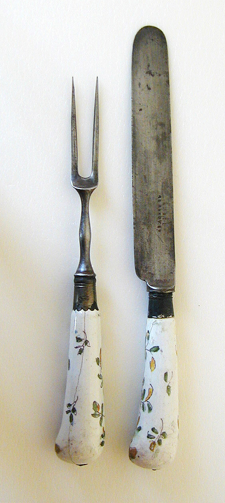 Two long curved tines, waisted shoulders, baluster neck. Silver ferrule, banded with scalloped edge. Pistol-shaped handle, earthenware, white ground with floral sprays in blue, yellow, green and purple. Small metal cap at the end of the handle.