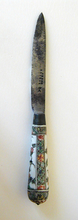 Leaf-shaped blade with straight upper edge. Plain bolster. Tapering silver ferrule with traces of gilding. Tapering porcelain handle with rounded end. Floral decoration, with birds and decorative bands along the sides, top and bottom of the handle in black, green, yellow, red and blue. (Famille Verte) Small botton cap at the end of the handle.
