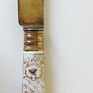 Leaf-shaped gilded blade, plain bolster. Banded ferrule, white porcelain handle, rectangular in section with polychrome decoration of birds on branches and butterflies, surrounded by a decorative pattern in gold.