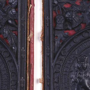Rectangular, front (a) and back (b) book covers of dark brown gutta-percha, each with large circular seal and heraldic device in center, within pierced design of foliage and acorns.  Each mounted on red paper and leather binding.  Marbleized end papers attached.