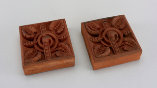 Square tiles with geometric, vegal shapes in relief.