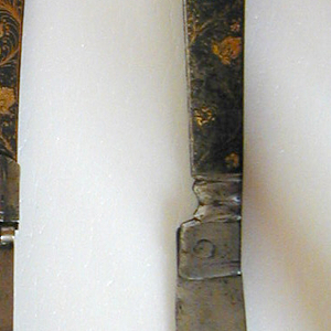 Fork has two flat tines, decorative chiseling at the join and a broad neck. Pistol-shaped flat handle with stylized floral damascening with gold flowers and cupid. Tines fold into handle. Brass rivets on handle.