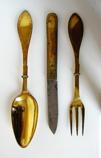 Leaf-shaped blade folds into flat, straight-sided handle with rounded end. Silver gilt handle engraved with floral pattern and decorative border. Three brass riverts.