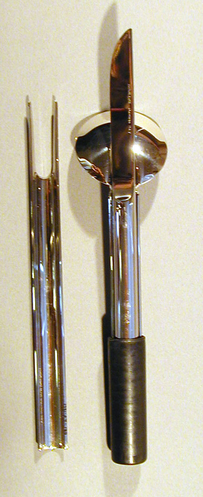 Short, hollow, black plastic cylinder with one open end into which the fork, spoon, and knife fit when assembled. Part of a four-piece traveling set with fork, knife, spoon, and holder.