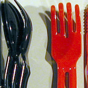 Red knife, teaspoon, tablespoon, fork and holder; each piece of cutlery has open handle into which holder slides, connecting all four utensils as nested stack.