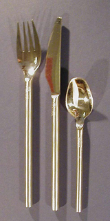 One piece spoon with slender, cylindrical handle of brushed steel with blunt end; polished steel bowl squared off at end.