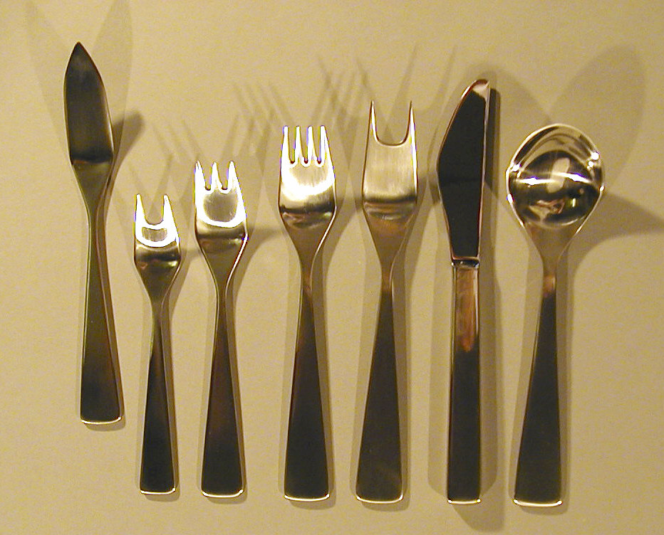 Integral piece. Flat, brushed steel handle, elongated pyramidal shape. Cold meat fork and small serving fork have 2 tines; fish fork has 3 short tines; dinner fork has 4 short tines.