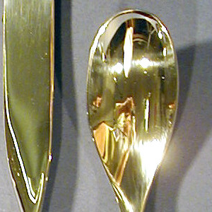 Mirror surface stainless steel. Tines and handle integral; three long tines, their base appearing to flow into single-twist at juncture with handle; handle oval in section flattened to plain truncated end.
