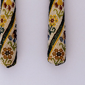 Two-tined fork, baluster stem. Tubular-tapered handle, beaded with multi-color floral bands in spirals, ground of white beads, blue, yellow and green beaded bands.