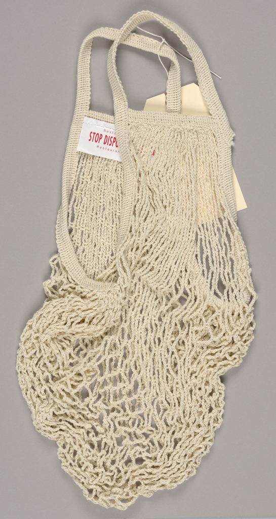 The present object, a natural cotton string bag of a type which Americans typically associate with Parisian market life, has a white, shiny fabric label attached by a row of machine stitches to the inside binding just below one of the two handles. Restaurant Florent/ Stop Disposable Culture/ Restaurant Bellevues are imprinted in red sans serif type, the second line in bold capitals and the first and third in miniature upper and lower case letters.