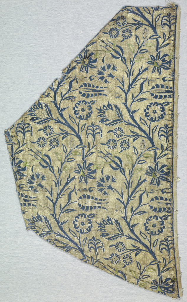 A ground of gold twill (metal very worn), with serpentine branches bearing carnation and lily blossoms primarily in blue, outlined with supplementary white weft. Other details of the design are worked in supplementary orange and green wefts (badly faded). Right selvedge present.