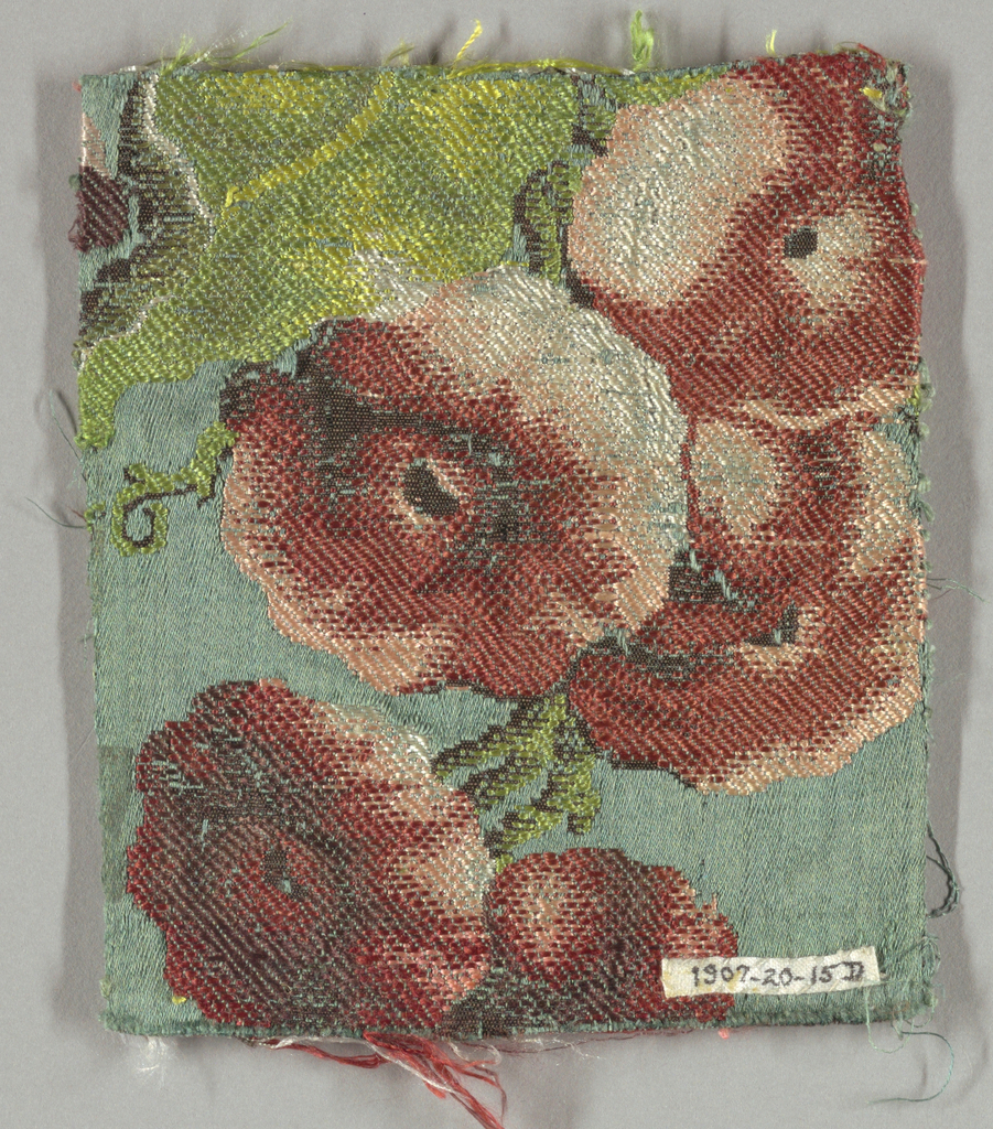Green satin ground with imcomplete design of large-scale flowers and smaller scale tree.  Design partly in white and brown secondary wefts and partly in polychrome brocading threads. c: has left selvage present.