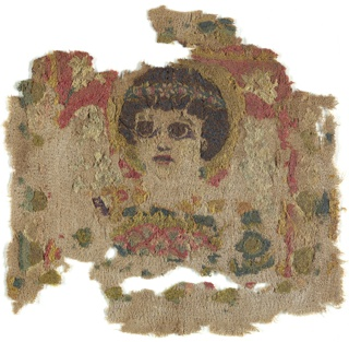 Bust of a female figure with dark hair and large dark eyes, a laurel wreath on the head, a halo, and wings, with a flower basket held under her chin. A single lily fills the corner above each wing. In dark blue, dark brown, greens, golden yellow, pink, and beige wool chain stitches on undyed linen plain weave, skillfully seamed. Eye whites embroidered in linen.  A few details in varied surface stitches.
