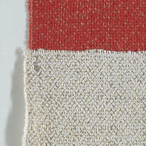 Samples of textured and metallic yarns side by side. Component A has a warp of red boucle yarns and a weft of smooth red yarns with flat metallic thread. Component B has a warp of off-white boucle yarns and a weft of smooth off-white yarns with flat metallic thread.