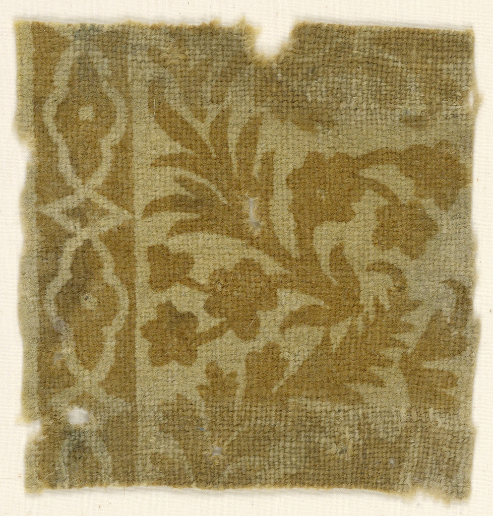 Coarse, cream-colored ground printed in reddish-brown. Pattern shows part of a floral spray and at one side, a section of border in a cartouche pattern.