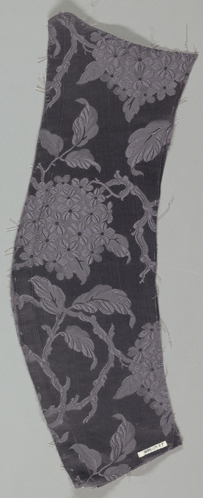 Portion of a dark mauve sleeve with self pattern in satin ground.