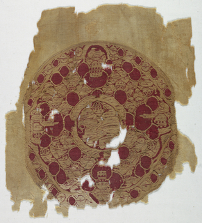 Tapestry-woven circular medallion in ivory and red wool on the warps of a weft-faced plain weave ivory wool fabric. A small roundel with a man mounted on a horse is surrounded by four figures, one on each of the four axes, in lobed frames which break into the outer border. The spaces between the four figures are filled with small figures and red circles. The outer border is made up of small red circles alternating with small blossoms.
