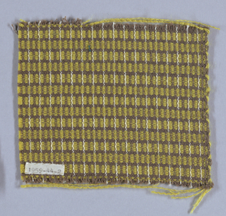 Brown wool warps in plain weave alternate with brown and yellow wefts. Yellow wefts float over two or three warps at a time, making horizontal yellow stripe. An ornamental white warp appears at regular intervals.