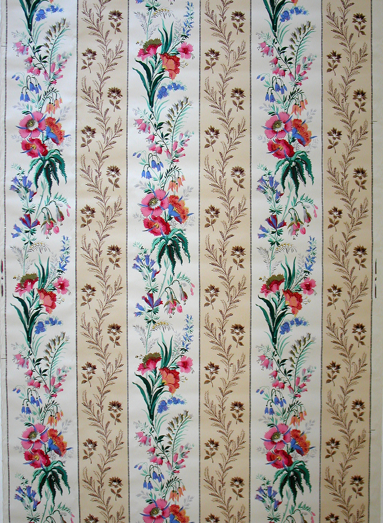 Wide cream-colored stripe with multi-colored flowers alternating with narrow tan stripe with ferns and floral motifs. Fine band of dentilling separating columns.