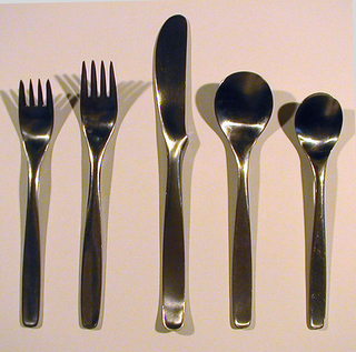 Dinner knife (a): flat strip of stainless steel with curved protrusion where blade merges into handle forming finger support; dinner fork, salad fork (b,c): each four-tined with slightly tapering, curved handle with rounded, square terminal, rectilinear handle, ovoid bowl; teaspoon, soupspoon (d,e): each with circular bowl and tapering stem with rounded, square terminal and rectilinear handle.