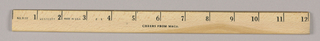 1993-151-33a - Ruler: Fabricated of blond wood and edged in brass-colored metal, the twelve inch ruler is marked off at one-inch intervals by the numerals 1-12 and by black lines, to the right of the numerals, extending downward about halfway. The message, Cheers from M&Co, is imprinted in small black capitals and is positioned underneath in the space between the numerals 5 and 7.  1993-151-33b - Wrapper: Two vertical slots are incised in each end of the principal surface, so that the two end flaps may be inserted in order to form a pyramidally-shaped container. A black and white illustration of the Eiffel Tower within an oval shape is centered on this surface. With the object turned so that the principal surface is now on bottom, the viewer faces a second surface, showing a quotation in the center, Imagination is more important than knowledge, from Albert Einstein, whose name is imprinted beneath in serif-style capitals. The third surface is blank, except for a vertical line of type along the left edge identifying the M&Co name and address.