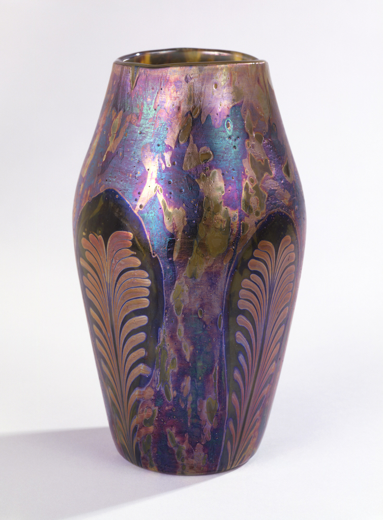 """Blown """"Cypriote"""" ware vase with curved shoulder. Neck tapered inward toward plain rim. Lustred in overall mottled iridescent pattern, with four oval reserve panels with lustre applied to suggest upright feather motif."""