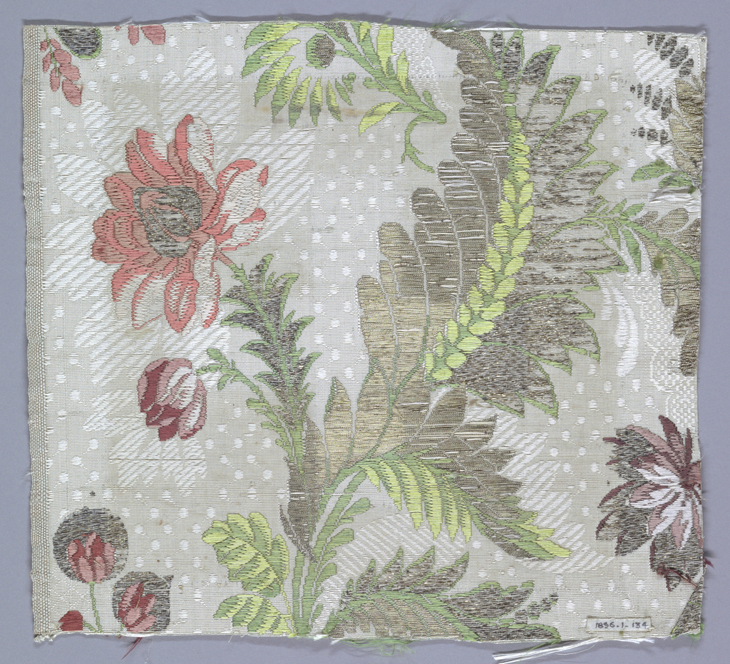 Fragment of brocaded silk. White and grey ground with details brocaded in metallic yarns and green and pink silk, showing a flowering plant on a dotted background. One selvage present.
