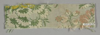 White ground.  Very imcomplete symmetrical floral design, partly in secondary green silk weft partly brocaded in coral, yellow, tan, beige and ivory.  Right selvage present.