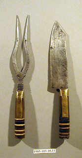 Large two-tined fork, tines curved and pointed. Bolster rectangular in section, deeply cut. Tang with button end. Handle eight-sided. Brass scales on major plane engraved with wriggle work; four sides of bone; two tang sides. Handle end with 22 laminated sections of tri-color horn and brass plates. Plain brass end.