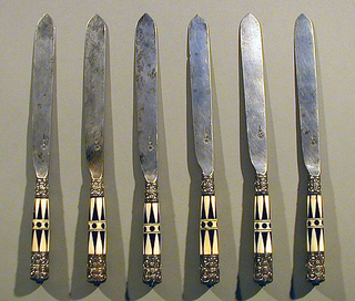 Blade with straight sides and leaf-shaped point, hollow bolster. Ferrules silver-gilt with floral pattern. Tapered handles of ivory and bone inlaid in triangular pattern. In middle of handle black inlaid dots and two horizontal bands. Silver-gilt caps with floral pattern on end of handle.