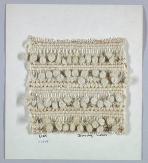 Warp of smooth two-ply yarn alternating with boucle yarn. Weft is repeating pattern, each unit containing two smooth synthetic yarns, one metal braided over a central core, one chenille, one paired narrow boucle yarns, two chenille, two paired boucle yarns and one woven ball fringe.