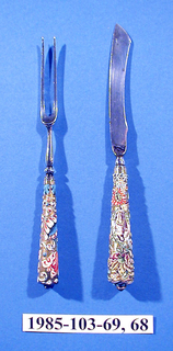 Small fork with two pointed tines. Baluster-shaped neck. Handle has gold enamel ground with floral pattern in red, white and blue. Blue rozette with red facetted stone on the top.