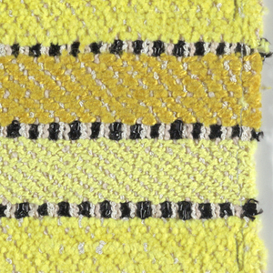 1/3 straight twill interrupted by one shot of plain weave with paired warps. Warp is white boucle alternating with beige boucle. Wefts have bands of various yellow yarns including two different 2-ply yarns, chenille, and two different shades of boucle. Yellow bands are divided by wefts of shiny black plastic in plain weave with paired warps.