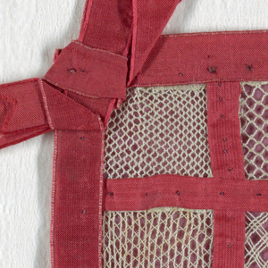 Sampler divided with red woven tape into a grid of sixteen squares, each square filled with a different needle lace pattern. With bows of red tape at the corners.