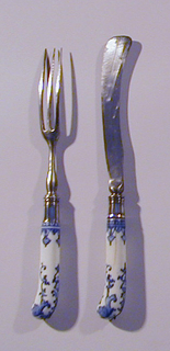 Saber-shaped blade with waisted bolster, plain silver ferrule with horizontal bands. Pistol-shaped white porcelain handle with dark blue floral and scrolled decoration. Button cap at the top of the handle missing.