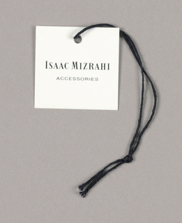 Isaac Mizrahi, in black Bodoni capitals, with the initial letters of both names in larger type, is centered on the white tag. Accessories, in smaller and lighter sans serif style capitals, is centered in the lower half. A black string, inserted in a small punched hole, centered near the top edge of the tag, is tied in a knot near the open end of the string.