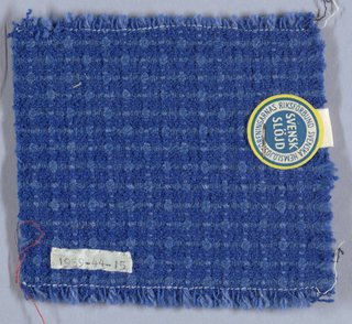 Two shades of blue cotton and wool threads, some heavily twisted, in vertical and horizontal stripes and a nubby-texture.